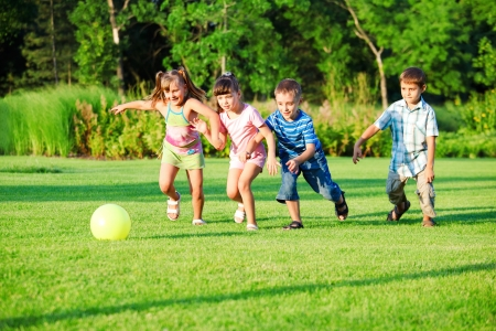 ni�os jugando en el parque: Grupo de ni�os jugando con la pelota en el patio trasero