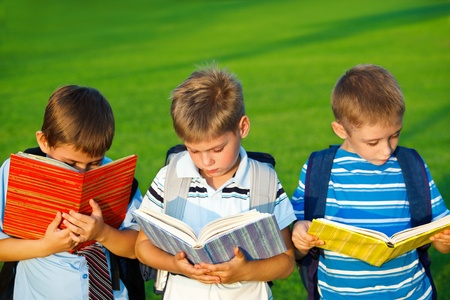 Three little students with books  in park photo