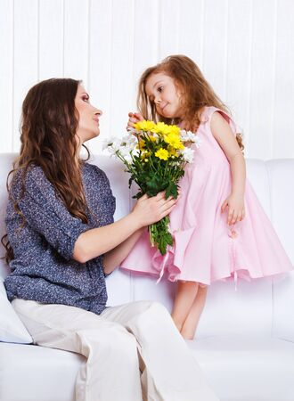 Mother holding flowers bunch, talking with little girl photo