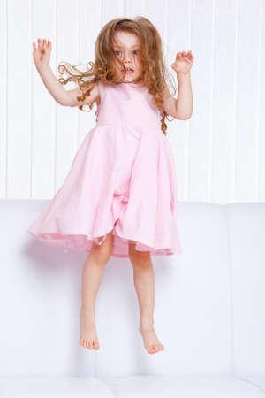 Sweet preschool girl jumping on the sofa Stock Photo - 9330574