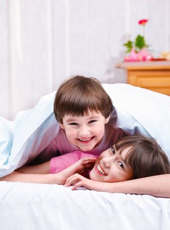 Happy brother and sister covered with blanket photo