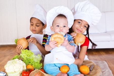 Three kids in white aprons and hats eating sandwiches photo