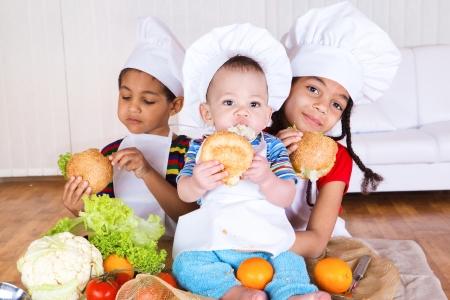 ni�os comiendo: Tres ni�os en delantales blancos y sombreros de comer bocadillos