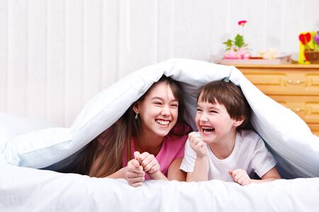 covered: Children in bed, laughing Stock Photo