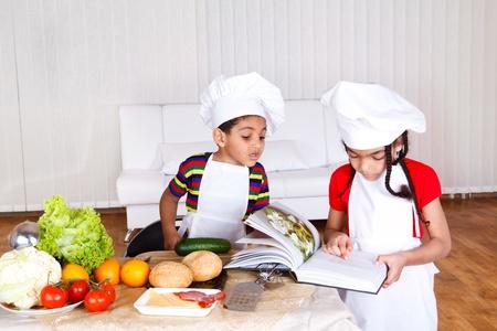 children cooking: Dos cocineros poco leyendo receta en un libro de cocina