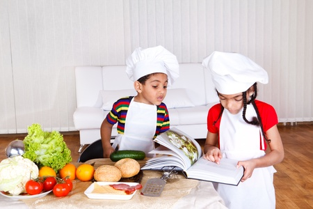 kids eating healthy: Two little cooks reading recipe in a cookbook