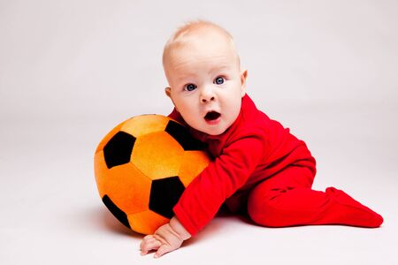 bebe gateando: Ni�o sorprendido con bal�n de f�tbol negro y naranja Foto de archivo