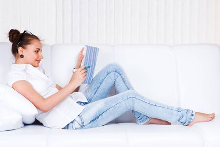 Female student reading on the sofa Stock Photo - 9354779