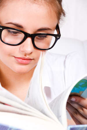 Portrait of a teenage girl in glasses turning book pages photo