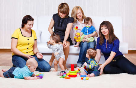 Mothers in the living room look at their babies playing Stock Photo