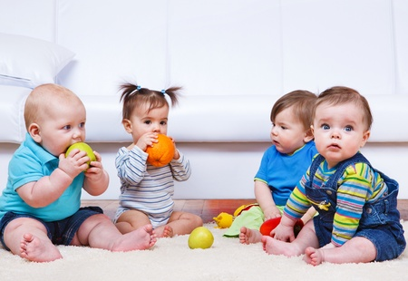 babies laughing: Four toddlers sitting in a lounge Stock Photo
