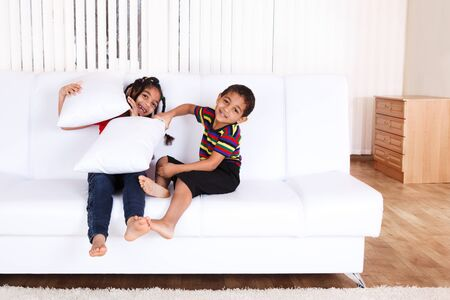 Cheerful brother and sister having pillow battle Stock Photo - 9444045