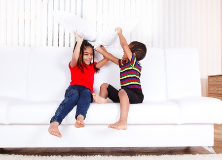 brother sister fight: Two african american kids playing with pillows
