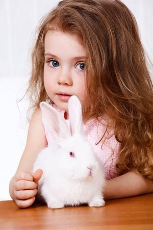 Preschool girl with long hair and a white rabbit sitting on the table photo