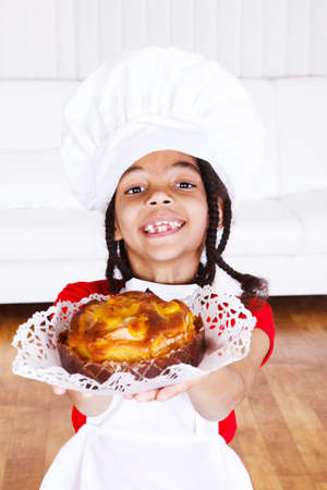 Smiling african american girl in apron and hat giving an apple pie photo