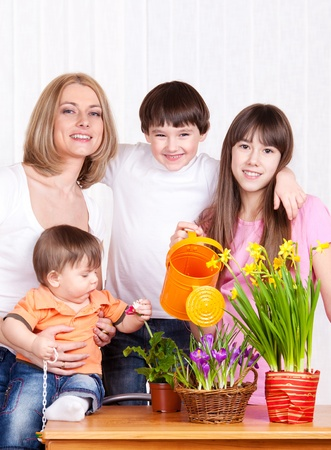 Family watering flowers at home photo