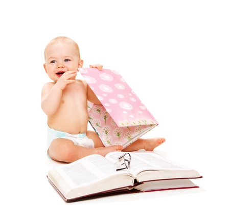 Laughing baby, open books beside him photo