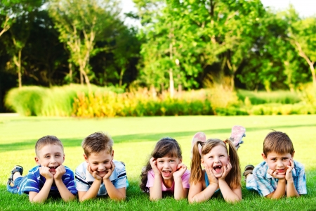 surprised child: Five preschool  kids laughing in the backyard Stock Photo