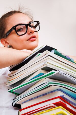 Portrait of a teenage girl and a books heap Stock Photo - 9476312