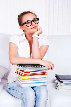 Smiling student in glasses sits on the sofa with books stack photo