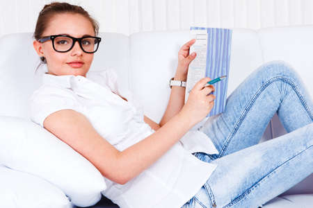 Student girl lying on the sofa and studying photo