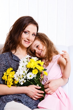 Happy mother holding flowers and embracing lovely daughter photo