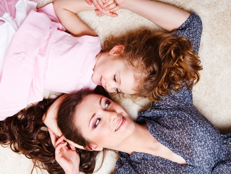 Little girl and mother lying on the carpet and looking at each other Stock Photo - 9476330