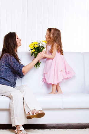 Beautiful preschool kid presenting flowers to mother photo