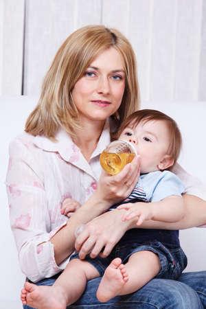 Bébé boire un jus sur les genoux de maman Banque d'images - 9476368