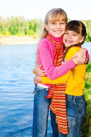 Cheerful kids in bright clothing embracing photo
