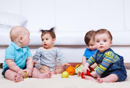 playing with baby: Gruppo di quattro bambini seduti sul pavimento