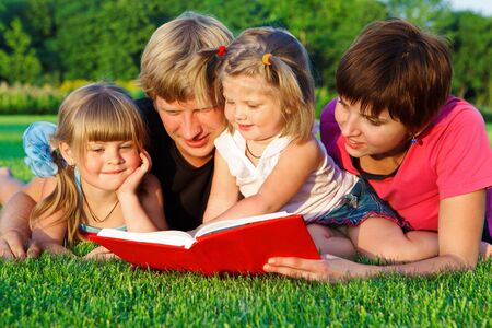 Parents and two preschool daughters reading a book in the backyard photo