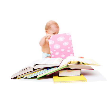 Baby in diaper looking attentively into the book photo