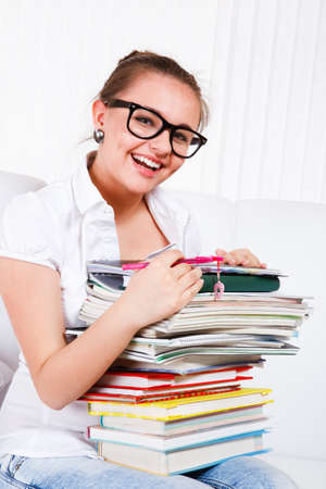 Laughing female student holding books heap on her knees photo