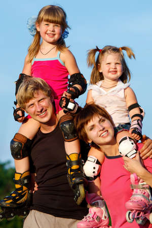Happy parents holding children in roller skates photo