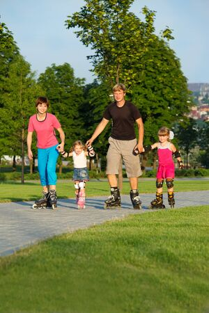 Parents and two preschool kids in roller skates Stock Photo - 9476335