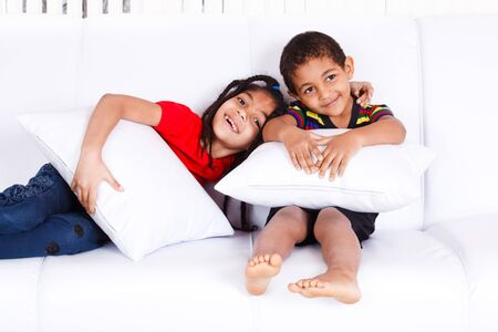 Two cheerful African-American children sitting on the sofa Stock Photo - 9528653