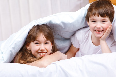 Brother and sister laughing, covered with blanket Stock Photo - 9528651