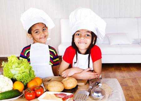 children cooking: Dos lindos afroamericanos poco cocineros, ingredientes para sandwich delante de ellos