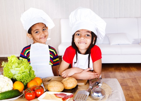 cooking ingredients: Two cute african american little cooks, ingredients for sandwich in front of them Stock Photo