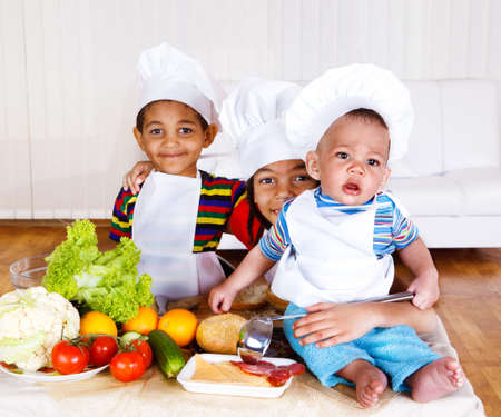 Three little cooks in white aprons and hats photo