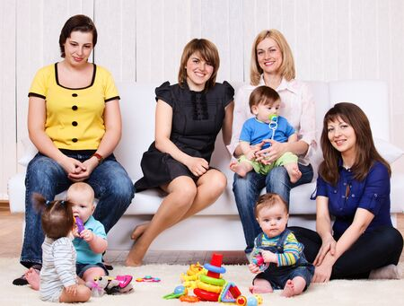 Female friends sit together with their babies photo