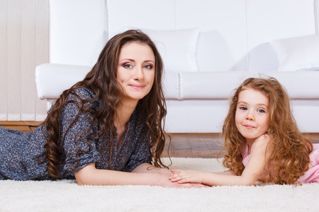 Pretty woman and sweet girl with long hair lying on the floor together.  photo