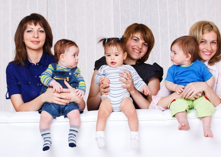 Three women and their babies on the sofa Stock Photo - 9587528