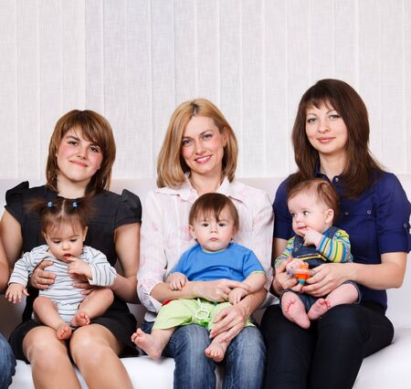 Three women sitting with babies on the sofa photo