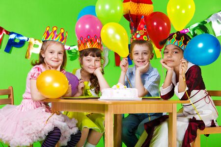 birthday party kids: Kids group sitting at the table with the birthday cake Stock Photo