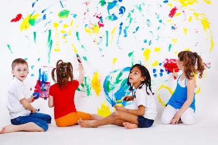 ni�os pintando: Cuatro ni�os de edad preescolares pintar la pared