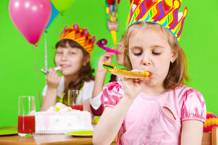 Girls in birthday crowns playing with party horns Stock Photo - 9587589