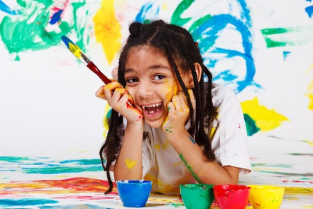 Happy african american girl lying on the floor with a paintbrush Stock Photo - 9587579