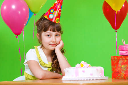 Sweet little girl in a party hat sits at the table photo